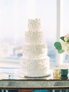 Four tier wedding cake adorn with fondant blossoms: http://www.stylemepretty.com/2017/02/16/modern-la-rooftop-wedding/ Photography: The Great Romance - http://thegreatromancephoto.com/