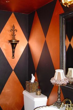 Black harlequin diamonds painted over a copper finish in a powder room