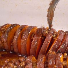 Drizzling hasselback-cut sweet potatoes with maple pecan mixture