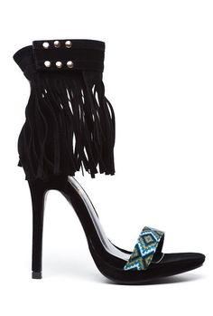 The Elsie Heel has a suede base which comes past your ankle and a adjustable ankle strap with black fringes. The strap across the toe area has a decorative pattern. The ankle strap has a velcro closur