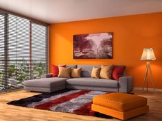 The slick orange wall and sofa stool stand out boldly in this living area. A few throw pillows are orange too, but they blend in with the red colors from the patterned floor rug, throw pillows and artwork . Daylight coming from the open blinds makes the whole place gleam.