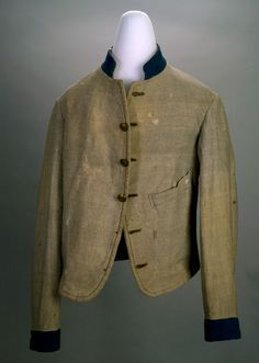 Confederate Uniform Coat of Gray Wool with Blue Trim. Referred to as a Columbus Depot Style Jacket. Originally had six buttons. One pocket on the left front .