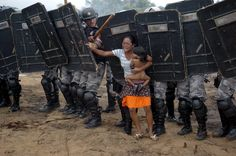 An indigenous woman holds her child while trying to resist the advance of Amazonas state policemen who were expelling the woman and some 200 other members of the Landless Movement from a privately-owned tract of land on the outskirts of Manaus, in the heart of the Brazilian Amazon, in this March 11, 2008 file photo. (Photo by Luiz Vasconcelos-A Critica/Reuters/AE)