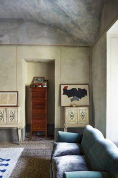 La maison de RobertoBaciocchi en Toscane Dans ce salon aux murs patinés et aux couleurs toujours d'origine, le mobilier fait partie de la collection personnelle du maestro, comme dans toute la maison. Le canapé est recouvert de velours, tissu de prédilection du décorateur pour sa capacité à refléter la lumière.