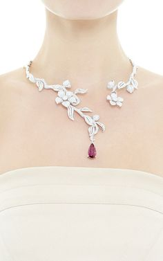 This necklace by **Wendy Yue** features a vine and flower neck encrusted with diamonds and a single rubelite stone dropping from the end set in 18k white gold.