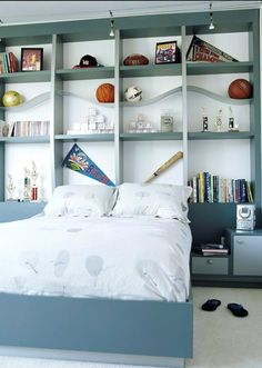 A Sporting Life!  A boys passion for athletics fueled tis room's decorating scheme. A floor to ceiling wall system, which doubles as an oversized headboard gives him a prominent place to display his sporting memorabilia.