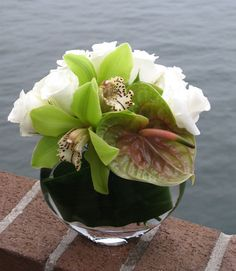 Modern and elegant arrangement of NYC fresh cut flowers including white Roses, Orchids, and Anthurium.