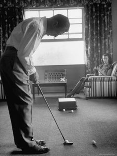 Ben Hogan putting in his living room with his wife.