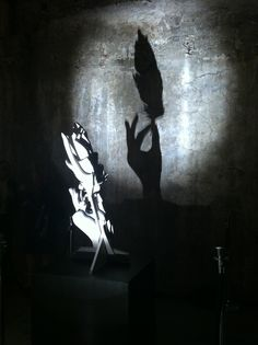 marble sculpture shadow revealed to be a hand and feather