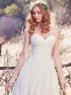 Maggie Sottero Wedding Dress Marta 7MS955, This vintage-inspired wedding dress features a ruched bodice, allover lace, and sheer pockets at the hip. A strapless sweetheart neckline and scalloped lace hemline evoke soft glamour. A-line lined with Viva Jersey for a luxe feel. Finished with covered buttons over zipper and inner elastic closure.