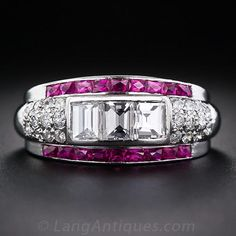 A dazzling and highly distinctive Art Deco three-stone diamond band style ring, hand fabricated in platinum, circa 1930s, centering on a bright-white and beautiful trio of large baguette, or emerald-cut diamonds, together weighing 1.00 carat. The three main diamonds are dressed up on each side with a glittering array of small round diamonds, and bordered top and bottom with a slender row of vibrant red French-cut calibre synthetic rubies.