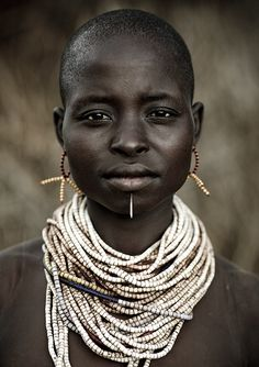 Karo woman - Omo Ethiopia    The Karo (or Kara), with a population of about 1000 - 1500 live on the east banks of the Omo River in south Ethiopia.   Their neighbors are the Hamar,Bana,Bashada,the famous Mursi and Nyangatom (on the other side of Omo river, who are their enemies ) . They speak a south Omotic language.  The Karo grow sorghum ,maize and beans... Photography by Eric Lafforgue
