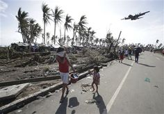 In this Monday, Nov. 11, 2013 file photo, survivors look up at a military C-130 plane as it arrives at typhoon-ravaged Tacloban city, Leyte province in central Philippines on Monday, Nov. 11, 2013. Haiyan slammed the island nation with a storm surge two stories high and some of the highest winds ever measured in a tropical cyclone. An untold number of homes were blown away, and thousands of people are feared dead. (AP Photo/Aaron Favila, File)