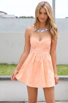 Peach coloured strapless dress and pastel coloured necklace.