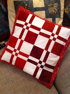 Red and white Disappearing Four Patch blocks made into a cushion cover.