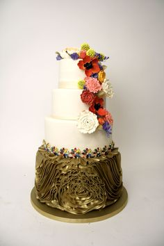 Charm City Cakes - Colorful flowers cascading down a four tier white and gold cake. We love the gold ruffles on the bottom tier of this cake!