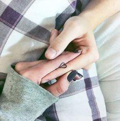 Personas uniendo sus tatuajes que forman un corazón