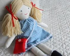 Traditional rag doll, little doll, cloth doll, doll for little girl, handmade soft toy  Rag Doll made from my own pattern with a cotton body stuffed with hollow fibre safety toy filling. She wears a pretty floral dress trimmed with cotton lace. Her feet are made with felt which are also trimmed with lace. Her yarn hair is tied in bunches, secured to the head and finished with ribbons. She comes ready with her own little felt bag. This little Rag Doll would make a wonderful gift for any…