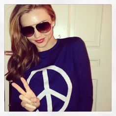 Miranda Kerr flashed a peace sign (while sporting a peace sign sweatshirt).