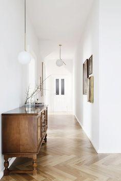Bright and white hallway with white walls and herringbone hardwood floors