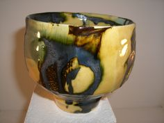 Tea bowl in earthenware. Faceted and decorated with poured slips, oxides and translucent glazes.
