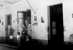 1935 Niños asomandose al interior de una vivienda en el patio de una vecindad.