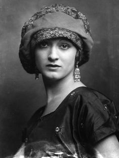A model wearing an elegant fabric hat and dangling diamond earrings, 1920.