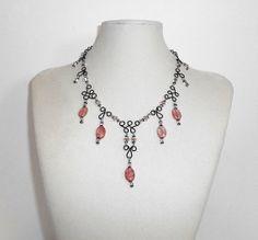 Rose quartz drops necklace. Swarovski crystals and black colored copper wire work.