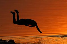 Allahabad, India: An Indian boy jumps into the Ganges River