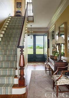 In the entry foyer, antique English wooden and brass candlestick lamps from Parc Moncea top an English console from English Accents Antiques; Oushak rug is from Keivan Woven Arts. Carpet Stair Treads, Carpet Stairs, Traditional Decor, Traditional House, Estilo Colonial, Foyer Decorating, Decorating Cakes, Decorating Ideas, Decor Ideas
