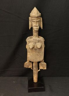 OLD FEMALE ROD PUPPET DANCE STAFF. Bamana people, Burkina Faso. Collected in a village near the Malian border. She wears a traditional hair style with braids. Arms attached to pulley-like articulations at shoulders are moved by pulling strings. On custom base. Wood, string. H 18 in.