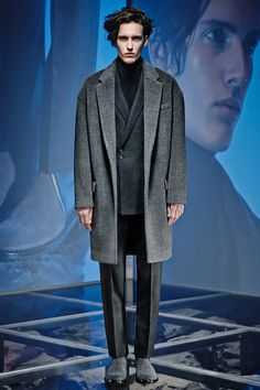 The background and model's face create fearful mood and coldness, but the fabric of coat, turtleneck shirt, and the way how he layered clothings look very warm. Oversize Jacket is well cordinated with double breasted suits and shades on grey tone color of clothes produce dramatic mood. Another good example of using long length coat to show styling. Balenciaga Fall-Winter 2014 Men's Collection