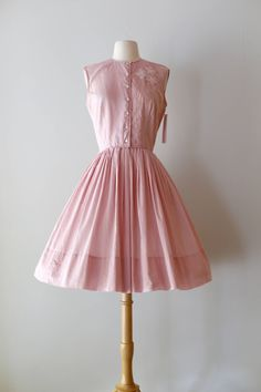 Beautiful 1950s peony pink cotton day dress with full pleated skirt. Features include a shirt waist bodice that buttons up the front. Pretty appliqué and beading on one side. 100% lightweight cotton is perfect for the summer. Would be perfect worn dressed up for a party or dressed down for a picnic! The perfect, versatile summer dress. ✂-----Measurements  Bust: 38 Waist: 28 Hips: open Length of skirt from waist to hem: 22.5  Label: none remaining Material: cotton Condition: Excellent…