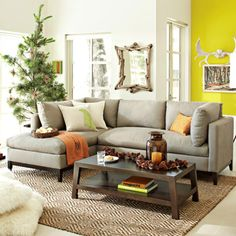 Love the sofa with a sunny mustard accent wall.