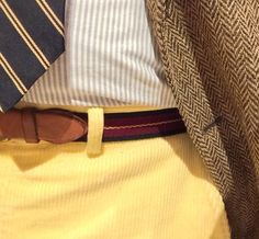 Light brown tweed jacket, white shirt with light blue dress stripes, navy tie with yellow stripes, yellow pants