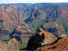 On the southwest side of Hawaii's island of Kauai, Waimea Canyon's deep gorge contrasts sharply with the lush green north shore coast and the adjoining rainforest of Koke'e State Park.