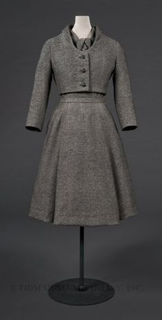 Virevolte suit, Christian Dior, Autumn/Winter 1955. Dior even went so far as to mimic the look of a neck-tie by tucking and pleating the fabric of the bodice to create a trompe l'oeil knot at the collar. Despite its serious appearance, this suit has a surprisingly lighthearted name: Virevolte. A French verb meaning to dance or twirl around