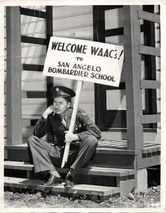 """1943- Soldier holding """"Welcome WAACs"""" sign on the steps of the new WAAC barracks at San Angelo Army Air Field."""