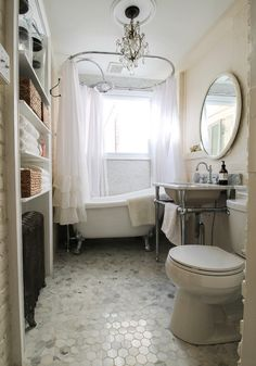 Soft pastels and timeless neutrals fill this small vintage bathroom with beauty. Its incredible clawfoot tub is the shining star of the space. Find this piece at Signature Hardware.