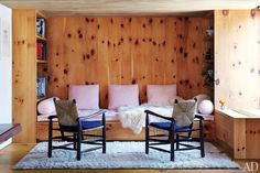 A seating area features armchairs by Perriand and a Moroccan Stripe carpet by Doris Leslie Blau.