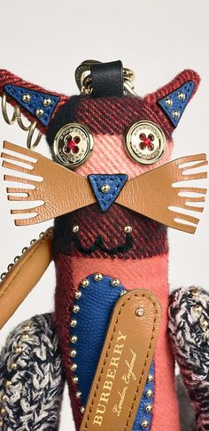 A charm in studded Scottish-woven cashmere and leather. The Burberry Clan is a group of charming creatures lost and found in our design studio. Playful mismatches of fabrics and fastenings are stitched together to create the whimsical new characters. Attach to a day bag for an animated accent. This is not a toy and it is intended for collectors of 14 years of age and above.