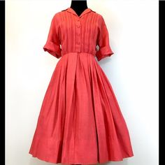 True Vintage 1950's Dark Coral Day Dress Dark coral textured cotton day dress from the 1950's. The pictures just don't do this frock justice! The color and material are crisp and bright, and the details at the chest and neck are absolutely delightful.  Bust 38-40 Snug 42 Waist 28-30 Length 40.5 with room to take the hem down by 4 inches.  No flaws found. Vintage Dresses
