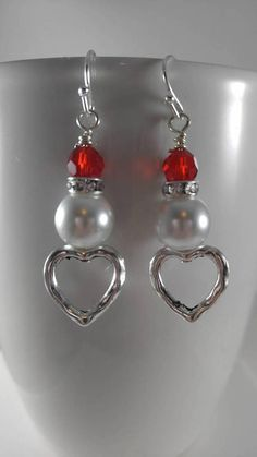 Hearts and love.. Earrings for her, for mom, or for you. These are great for the New Year, Valentines Day or everyday wear. They measure approximately 2 inches from top of hook to end of design. They are made with silver plated, metal hearts, glass pearls, rhinestone rondelles and red