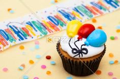 close-up of a cupcake with balloon design. - Close-up shot of a cupcake with colorful balloon shape and happy birthday sign in background.