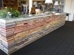 Library desk made from recycled books - After a devastating fire in the Architecture building burned down a portion of the library, Delft University of Technology in the Netherlands purchased a new collection to replace the old volumes. Instead of throwing away the old, unburned books, they stacked them up to create this awesome administrative desk, which they appropriately placed in the library.