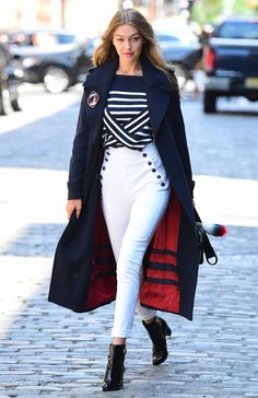 Gigi Hadid on the set of a photoshoot in New York wearing a nautical stripe jumper, white skinny cut trousers with pirate pockets, and black patent ankle boots. Plus a massive navy blue overcoat...