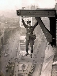 1920's photo of a member of NYC's aerial police literally hanging around over Times Square.