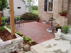no porch no problem create the porch feeling with a patio in the front yard, he raised planter of natural stone helps to define the outdoor room space,