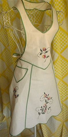 This looks like a halter dress when on, and has a very nice feminine dress shape. There is a small front pocket. The neck opening is a solid piece, which is slipped on, the only ties are ate the waist. The bottom edges are scalloped and it is all trimmed in jadeite green. The base fabric is a natural cotton, the kind that has little flecks of brown in it.