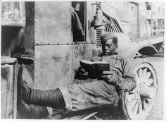 Reading a salvage book by one of the Salvage men on the salvage truck of the A.T.S. salvage office. St. Nazaire. c1919.  Library of Congress Prints and Photographs Division.